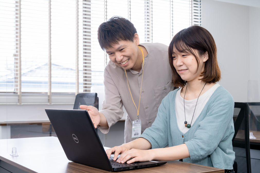 ノートパソコンを使う利用者に指導する職員